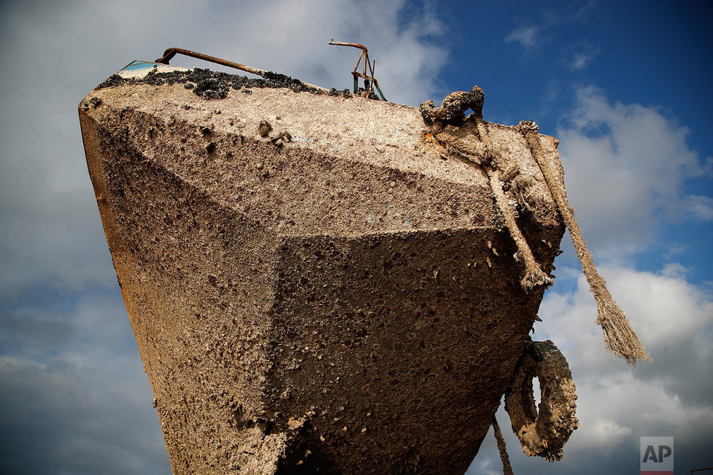 In this Wednesday, Dec. 19, 2018 photo, a small boat, that was recovered after spending years as a shipwreck is photographed at a dock in Elefsina, west of Athens. (AP Photo/Thanassis Stavrakis)