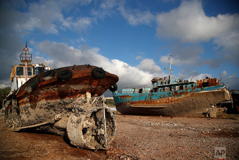 In this Wednesday, Dec. 19, 2018 photo, small boats, that were recovered after spending years as shipwrecks are photographed at a dock in Elefsina, west of Athens. (AP Photo/Thanassis Stavrakis)