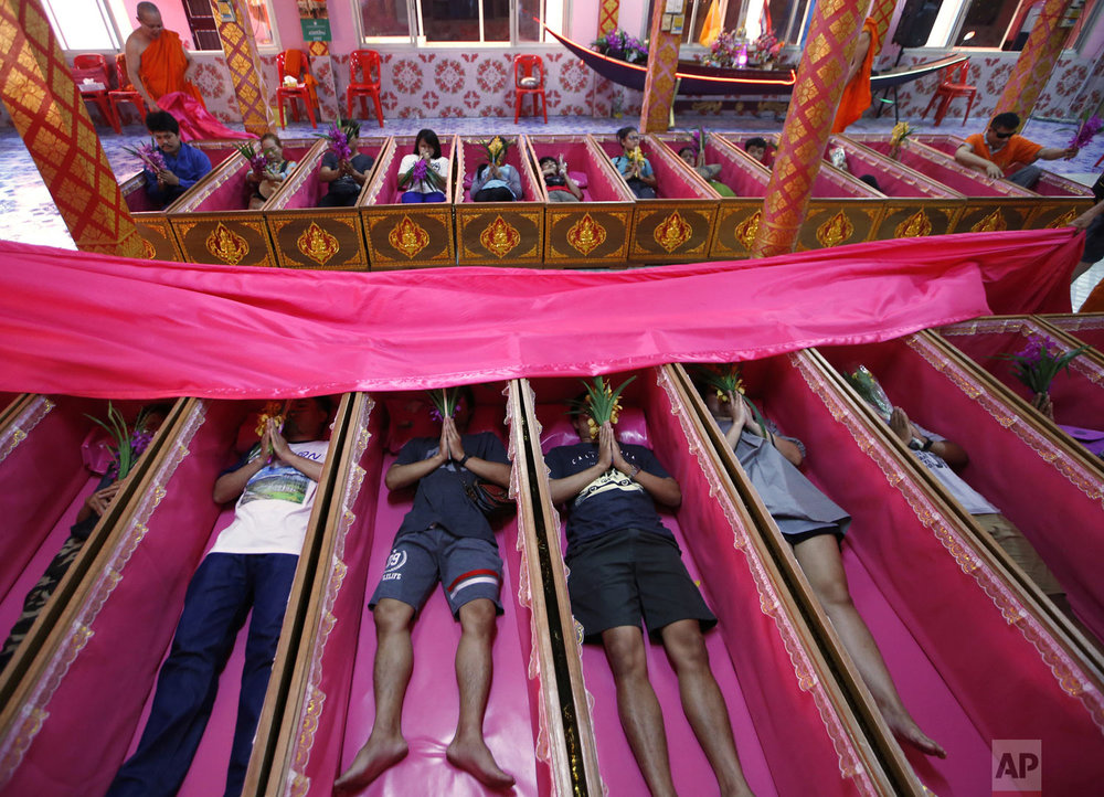 People pray as they take turns lying inside coffins at the Takien temple in suburban Bangkok, Thailand on Monday, Dec. 31, 2018. Worshippers believe that the ceremony – symbolizing death and rebirth – helps them rid themselves of bad luck and gives them a fresh start in the new year. (AP Photo/Sakchai Lalit, File)