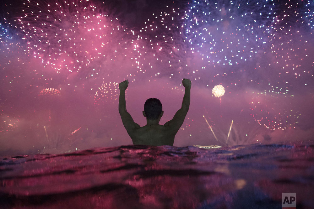 A man stands in the water as he watches fireworks over Copacabana Beach during New Year's celebrations in Rio de Janeiro, Brazil, Tuesday, Jan. 1, 2019. (AP Photo/Leo Correa)