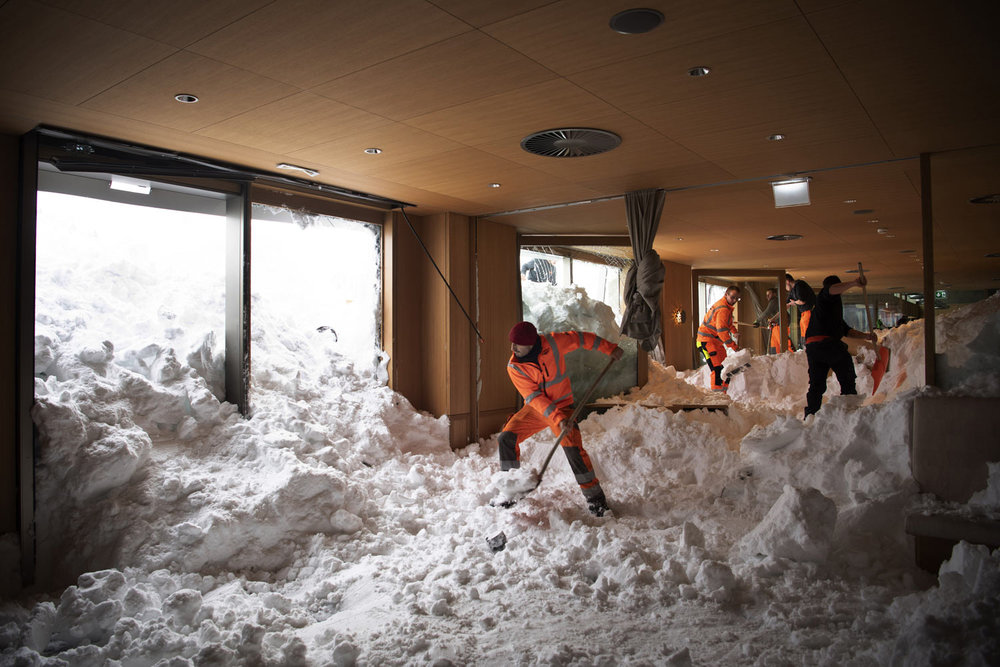 People clear snow from inside the Hotel Saentis in Schwaegalp, Switzerland, on Friday Jan. 11, 2019, after an avalanche. Police said three people were slightly hurt when the avalanche struck on Thursday afternoon. (Gian Ehrenzeller/Keystone via AP)