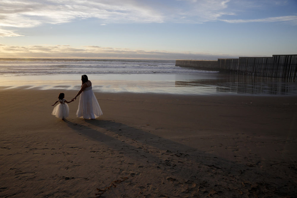 Ileze Dariel, of Tijuana, Mexico, reaches for the hand of her daughter, Jimena, as they wait for their photographer while taking family pictures on the beach next to the border wall, right, Wednesday, Jan. 9, 2019, in Tijuana, Mexico. (AP Photo/Gregory Bull)