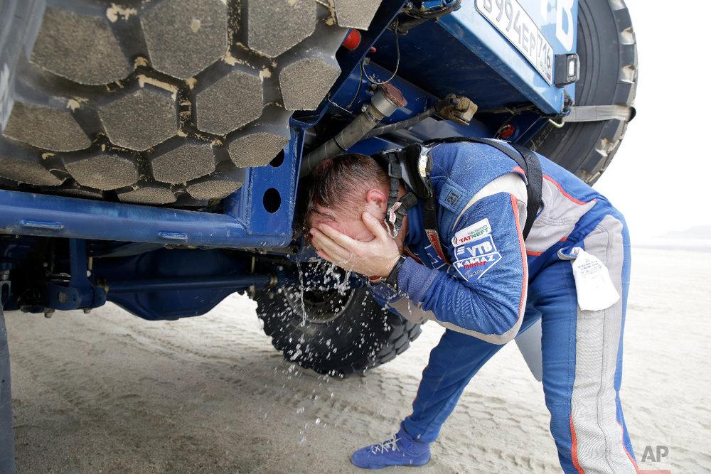 Kamaz truck driver Eduard Nikolaev, of Russia, refreshes at a stop during the stage eight of the Dakar Rally between San Juan de Marcona and Pisco, Peru, Jan. 15, 2019. (AP Photo/Ricardo Mazalan)