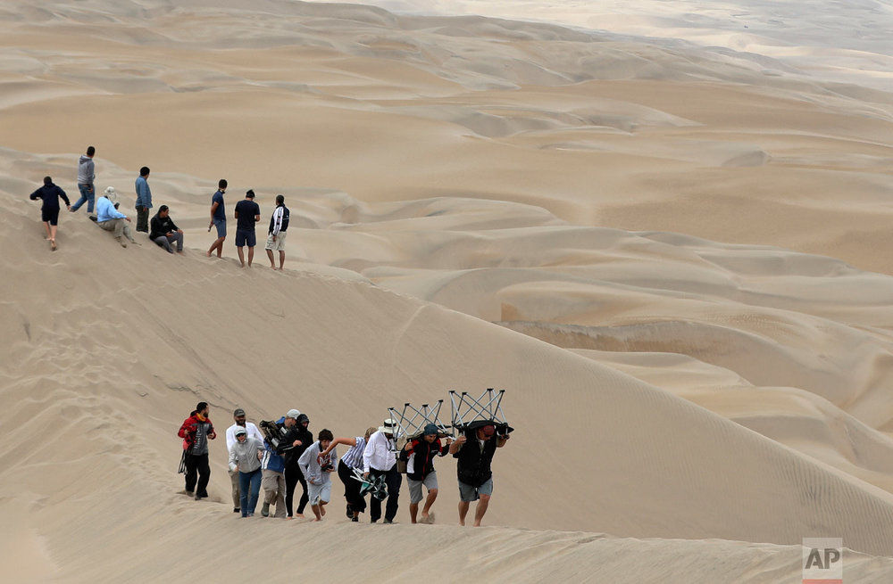 Spectators, some carrying chairs on their backs, scout for a good spot on the dunes to watch stage six of the Dakar Rally between Arequipa and San Juan de Marcona, Peru, Jan. 13, 2019. (AP Photo/Ricardo Mazalan)