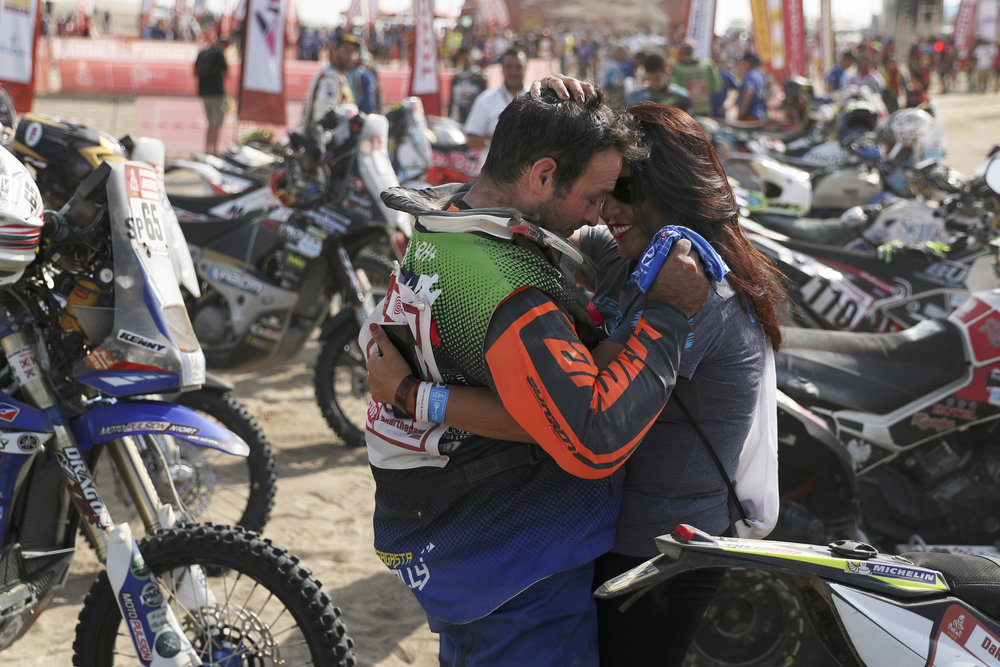 Chile's Yamaha quad rider Luis Barahona is embraced by his wife after placing 7th at the end of the Dakar Rally in Pisco, Peru, Jan. 17, 2019. (AP Photo/Ricardo Mazalan)