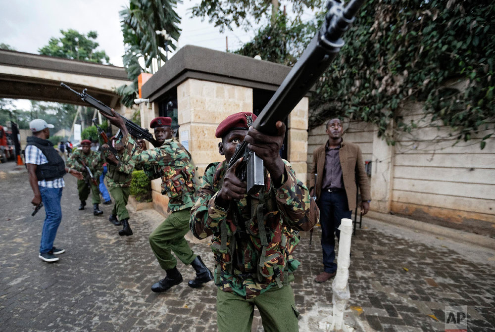 Kenyan security forces aim their weapons up at buildings as they run through a hotel complex in Nairobi, Kenya, Jan. 15, 2019. (AP Photo/Ben Curtis)