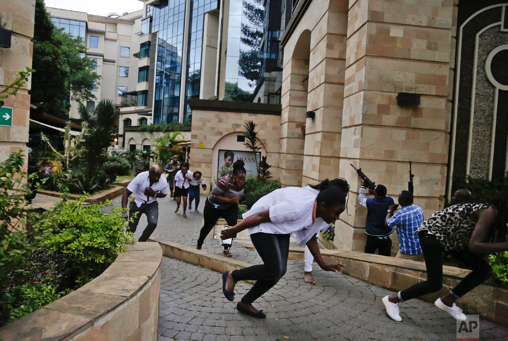 Civilians flee as security forces aim their weapons at the buildings of a hotel complex in Nairobi, Kenya, Jan. 15, 2019. (AP Photo/Khalil Senosi)