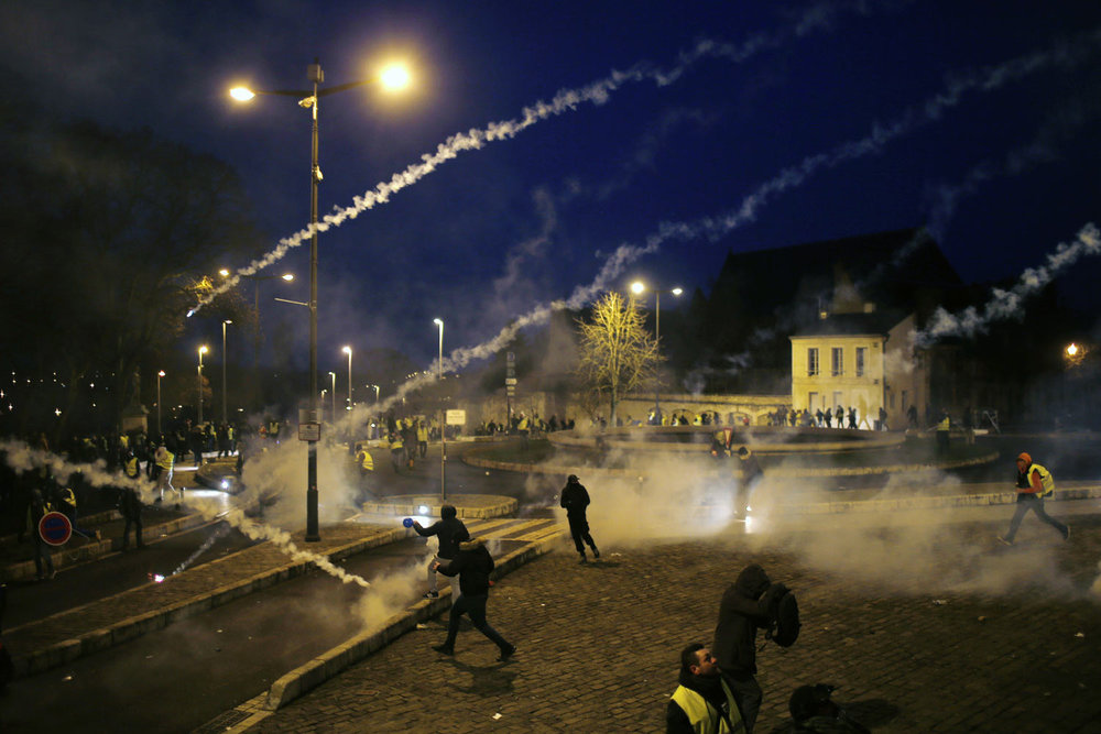 "Police fire tear gas grenades during a demonstration in Bourges, central France, Saturday, Jan. 12, 2019. The ""yellow vest"" movement is protesting President Emmanuel Macron's policies, seen as favoring the rich. (AP Photo/Rafael Yaghobzadeh)"
