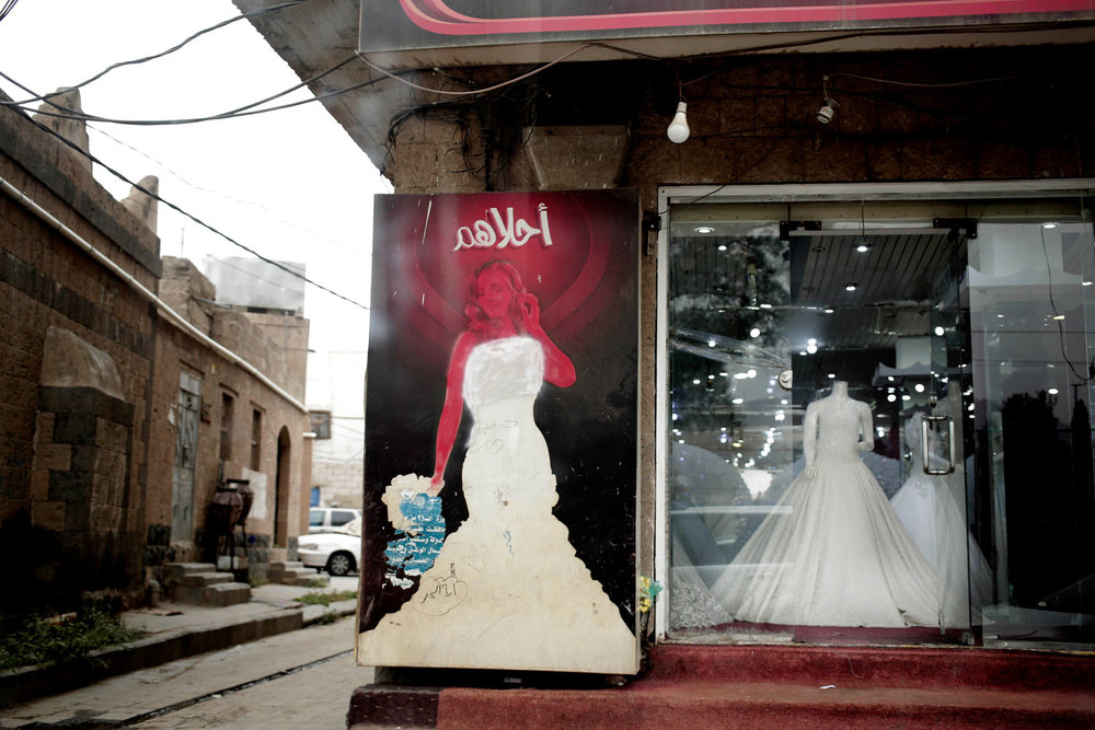 This Aug. 5, 2018 photo, shows a wedding boutique with a defaced advertisement of a model on a placard, in Sanaa, Yemen. Most wedding boutique advertisements showing women models are defaced in the capital city. (AP Photo/Nariman El-Mofty)