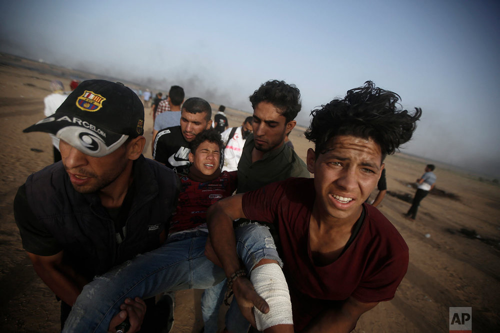 Palestinian protesters evacuate a wounded youth near the Gaza Strip's border with Israel, during east of Khan Younis, in the Gaza Strip, May 25, 2018. (AP Photo/Adel Hana)