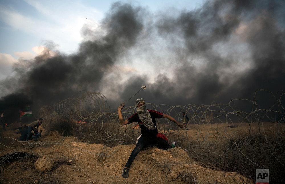 A Palestinian protester hurls stones towards Israeli troops at the Gaza Strip's border with Israel, Oct. 19, 2018. (AP Photo/Khalil Hamra)