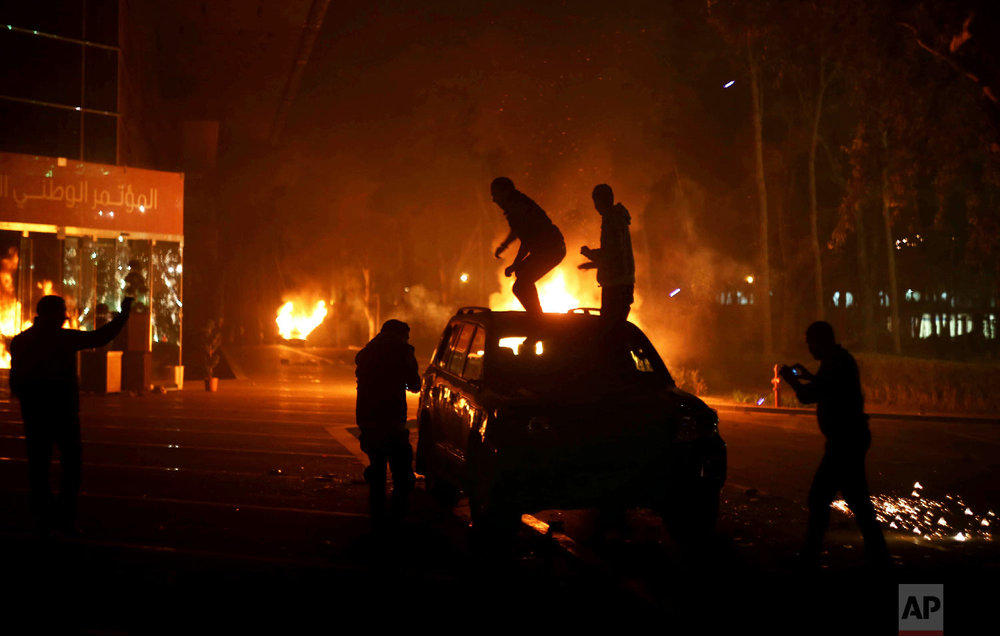 Protesters stand atop a vehicle as others burn in front of the National Conference Hall, in Tripoli, Libya, March 2, 2014.  (AP Photo/Mohamed Ben Khalifa)