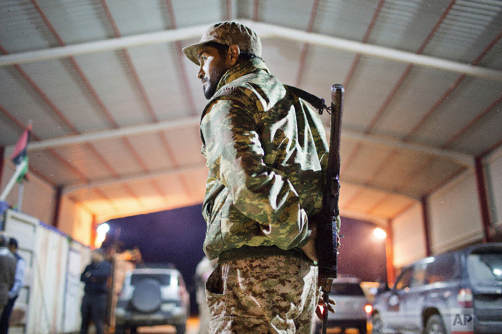 A Libyan military soldier stands guard at the entrance of a town, 110 kilometers (68 miles) from Sirte, Libya, Wednesday, Feb. 18, 2015. (AP Photo/Mohamed Ben Khalifa)
