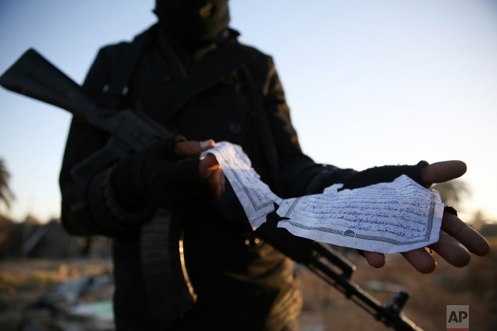 A member of the Libyan security forces displays part of a document in Arabic describing weaponry, that was found at the site of U.S. airstrikes on an Islamic State camp that killed dozens, near the western city of Sabratha, Libya, Feb. 20, 2016. (AP Photo/Mohamed Ben Khalifa)