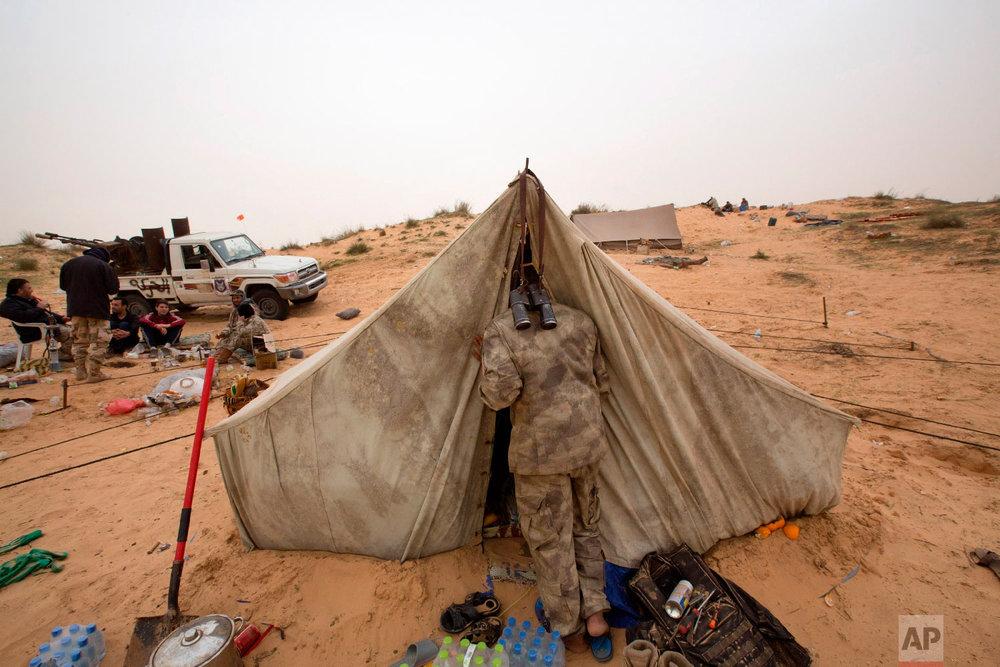 A Libyan soldier wakes his comrade in Al Ajaylat, 120 kilometers (75 miles) west of Tripoli, Libya, Saturday, Feb. 21, 2015.  (AP Photo/Mohamed Ben Khalifa)