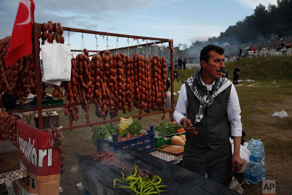A vendor offers sausages for sale to spectators during Turkey's largest camel wrestling festival in the Aegean town of Selcuk, Turkey, Sunday, Jan. 20, 2019. (AP Photo/Lefteris Pitarakis)