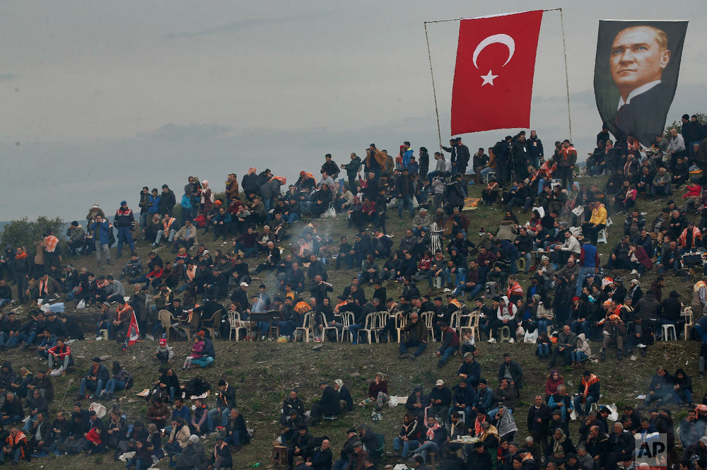 A Turkish flag and a poster of modern Turkey's founder Mustafa Kemal Ataturk are displayed on a hill full of spectators overlooking an arena where camels wrestle during Turkey's largest camel wrestling festival in the Aegean town of Selcuk, Turkey, Sunday, Jan. 20, 2019. (AP Photo/Lefteris Pitarakis)
