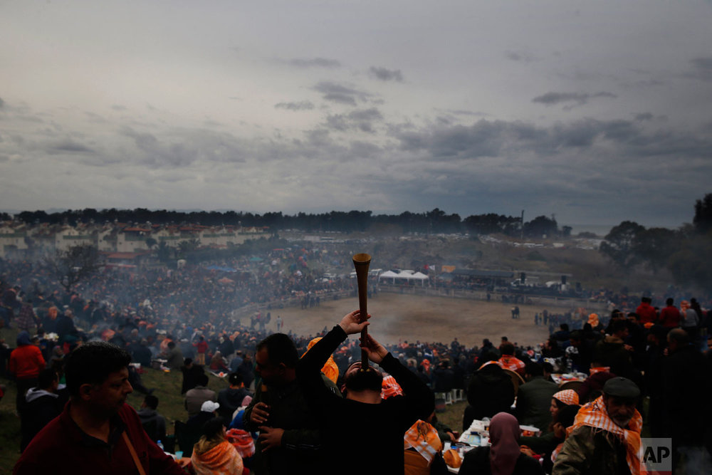 A musician performs traditional folk songs, as spectators enjoy on the hill overlooking the arena where camels wrestle during Turkey's largest camel wrestling festival in the Aegean town of Selcuk, Turkey, Sunday, Jan. 20, 2019. (AP Photo/Lefteris Pitarakis)