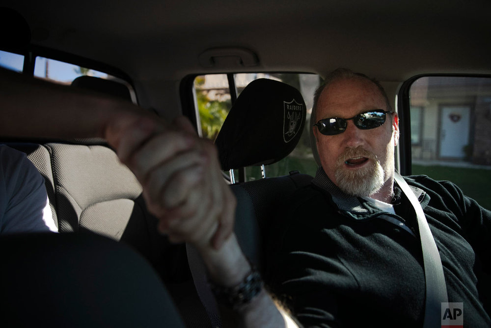 Chris George, a federal employee furloughed from his job as a forestry technician supervisor for the U.S. Department of Agriculture Forest Service, shakes hands with a passenger in his pickup truck while driving for Lyft to make ends meet Monday, Jan. 21, 2019, in Redlands, Calif. (AP Photo/Jae C. Hong)