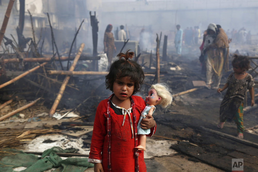 A young girl holds her doll while standing amid the ruins of her burnt home after a fire gutted the area, in Karachi, Pakistan, Sunday, Jan. 20, 2019. About 40 huts were burned to ashes as fire erupted early Sunday morning, making dozens of families homeless in a slum, local media reported. (AP Photo/Fareed Khan)
