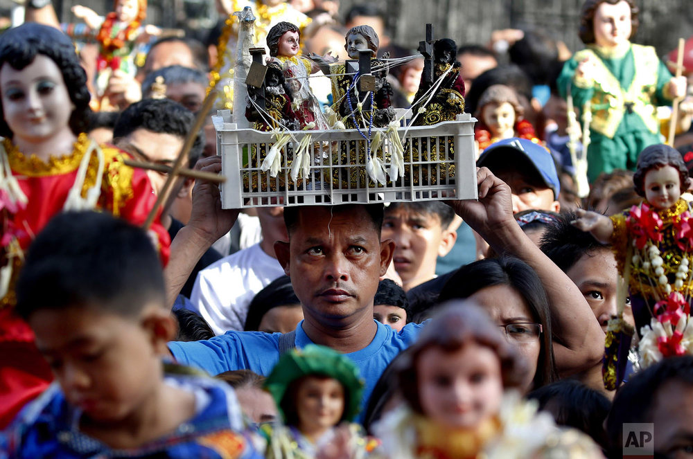 Roman Catholic devotees raise hundreds of images of the Child Jesus, known as Santo Niño, as they are blessed with holy water to celebrate its feast day in Manila, Philippines, on Sunday, Jan. 20, 2019. Many parishes around the country whose patron saint is the Child Jesus take part in the celebration which culminates in a Mass and procession. (AP Photo/Bullit Marquez, File)