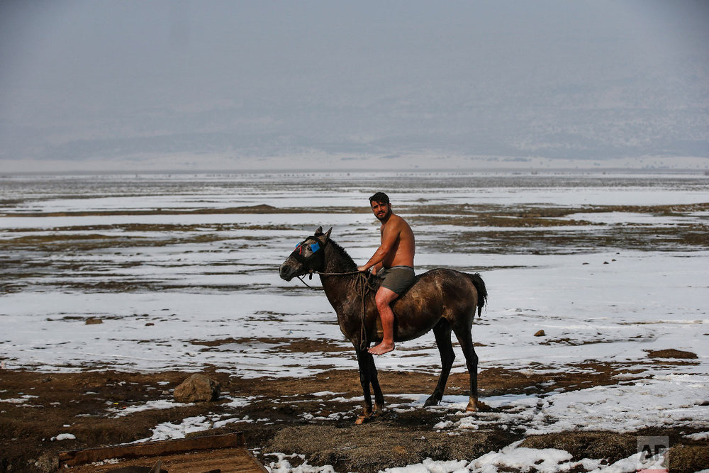 Muhammed Toren rides his horse after a bath in a hot spring along with his water buffaloes near the village of Budakli, in the mountainous Bitlis province of eastern Turkey, Thursday, Jan. 24, 2019. (AP Photo/Emrah Gurel)
