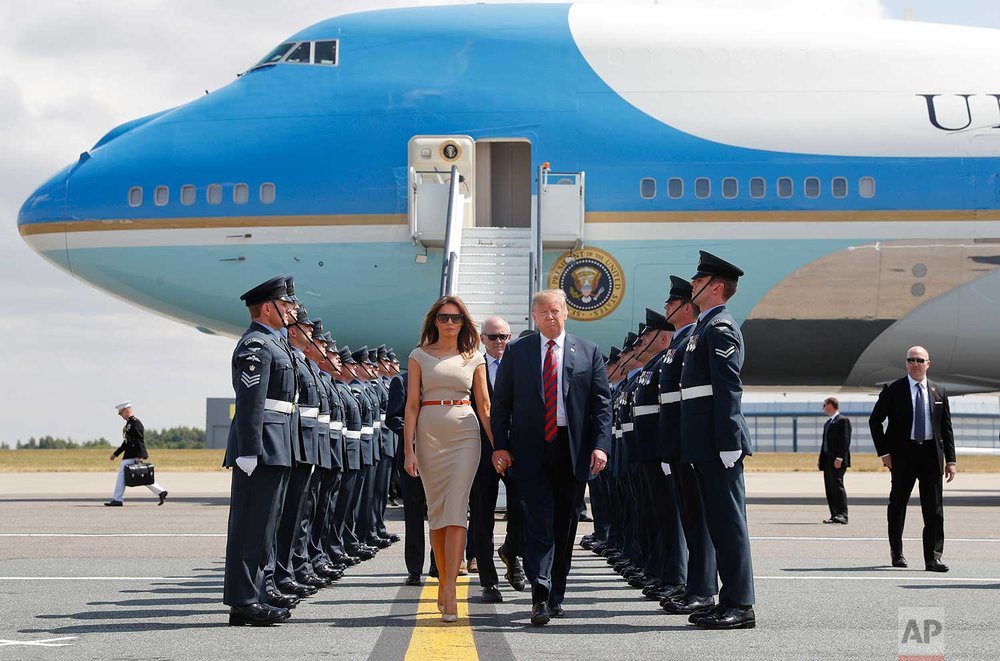 U.S. President Donald Trump and first lady Melania Trump walk across the tarmac after stepping off Air Force One as they arrive at London's Stansted Airport, Thursday, July 12, 2018. Walking directly behind them is Woody Johnson, center, United States Ambassador to the United Kingdom. (AP Photo/Pablo Martinez Monsivais)