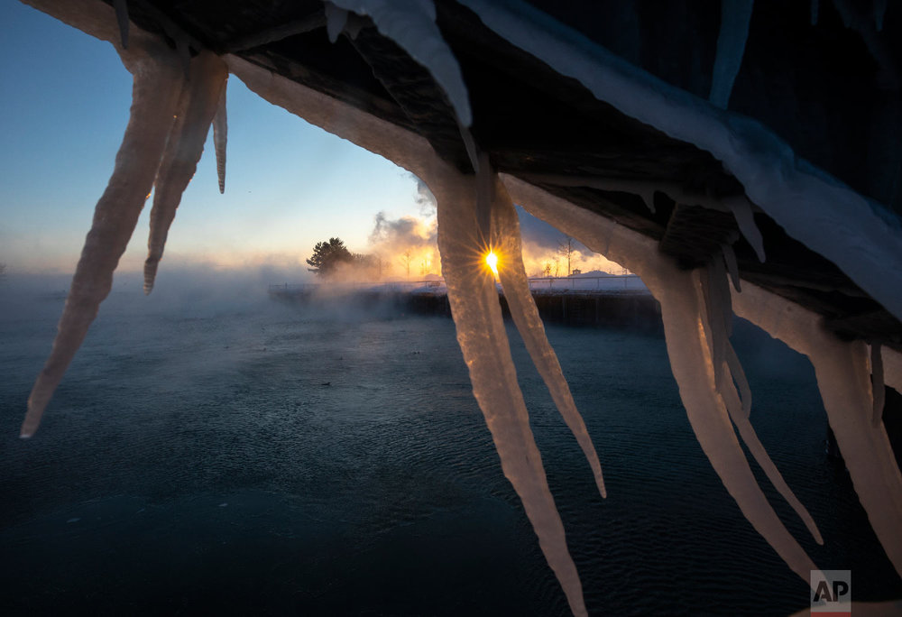 The sun rises behind icicles formed on the harbor in Port Washington, Wis., on Wednesday, Jan. 30, 2019. (AP Photo/Jeffrey Phelps)