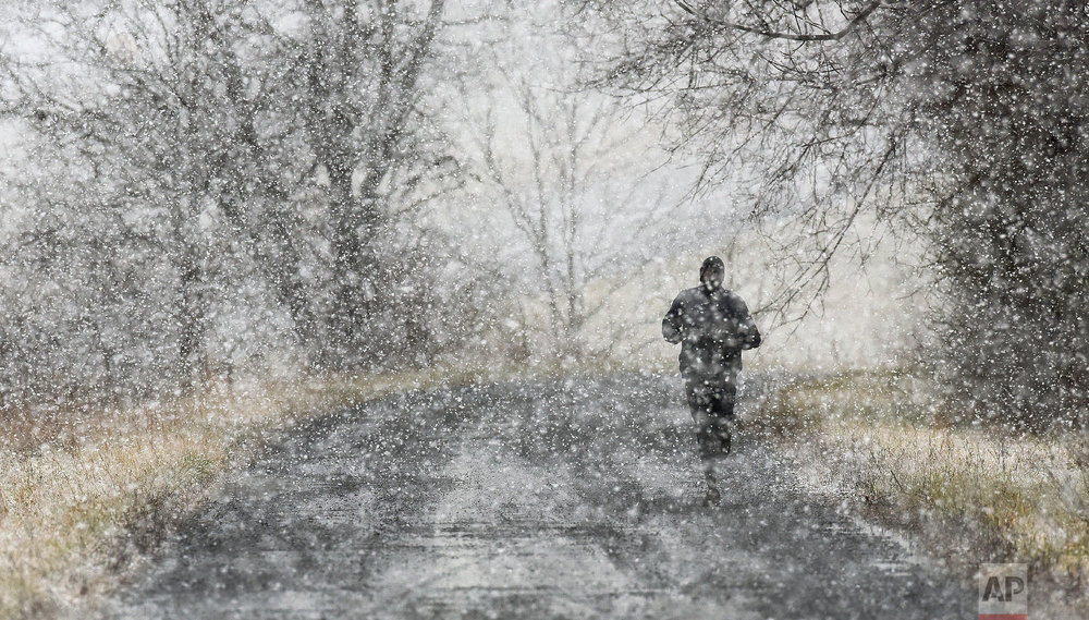 David Cheromei, Emory & Henry (VA) College Head Cross Country/Track & Field Coach, goes for a run on Itta Bena Road in Emory, Va. during a heavy snow fall Tuesday, Jan. 29, 2019. (Andre Teague/Bristol Herald Courier via AP)