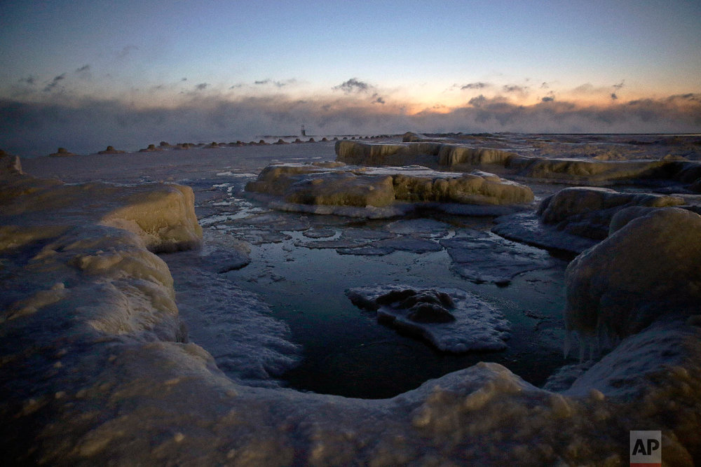 Ice forms along the shore of Lake Michigan before sunrise, Wednesday, Jan. 30, 2019, in Chicago. (AP Photo/Kiichiro Sato)