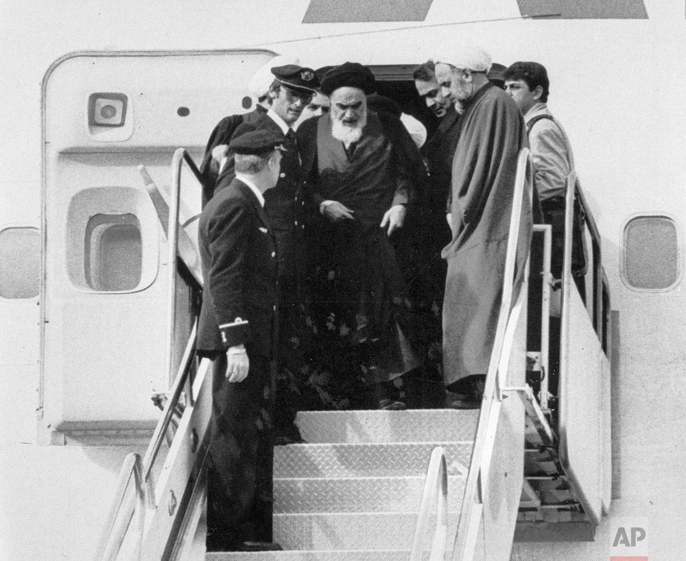 In this Feb. 1, 1979 photo, Ayatollah Ruhollah Khomeini, Iran's exiled religious leader, emerges from a plane after his arrival at Mehrabad airport in Tehran, Iran. Friday, Feb. 1, 2019, marks the 40th anniversary of Khomeini's descent from the chartered Air France Boeing 747, a moment that changed the country's history for decades to come. (AP Photo)