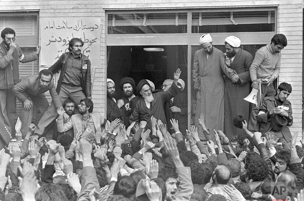 In this Feb. 1, 1979 photo, Ayatollah Ruhollah Khomeini, center, waves to followers as he appears on the balcony of his headquarters in Tehran, Iran. (AP Photo/Campion)