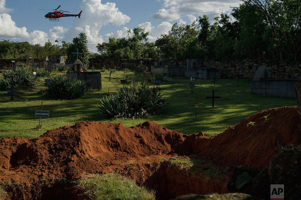 Empty graves lie open as a a helicopter carrying a body pulled from the mud, days after a Vale dam collapsed, flies over a cemetery in Brumadinho, Brazil, Jan. 28, 2019. (AP Photo/Leo Correa)
