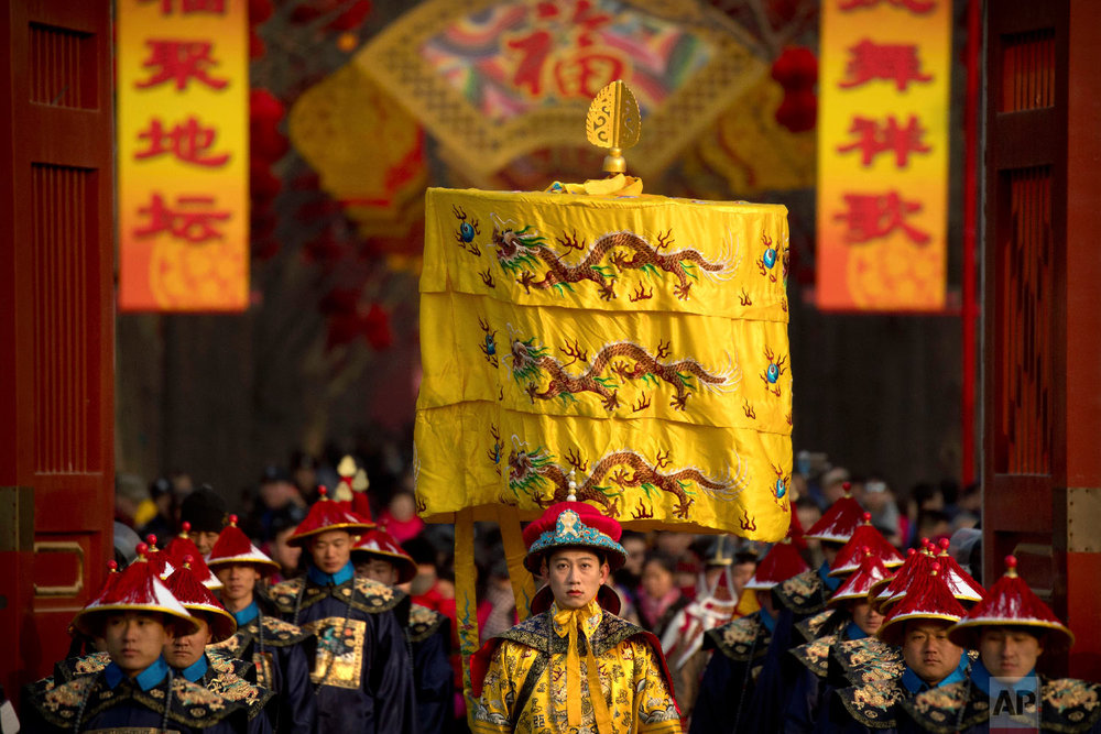 A performer dressed as an emperor, center, participates in a Qing Dynasty ceremony in which emperors prayed for good harvest and fortune at a temple fair in Ditan Park in Beijing, Tuesday, Feb. 5, 2019.  (AP Photo/Mark Schiefelbein)