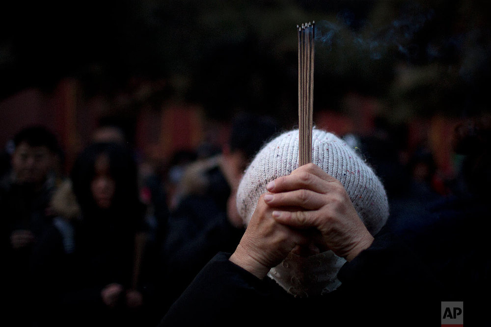 A  woman holds sticks of incense as she prays at the Lama Temple in Beijing, Tuesday, Feb. 5, 2019.  (AP Photo/Mark Schiefelbein)