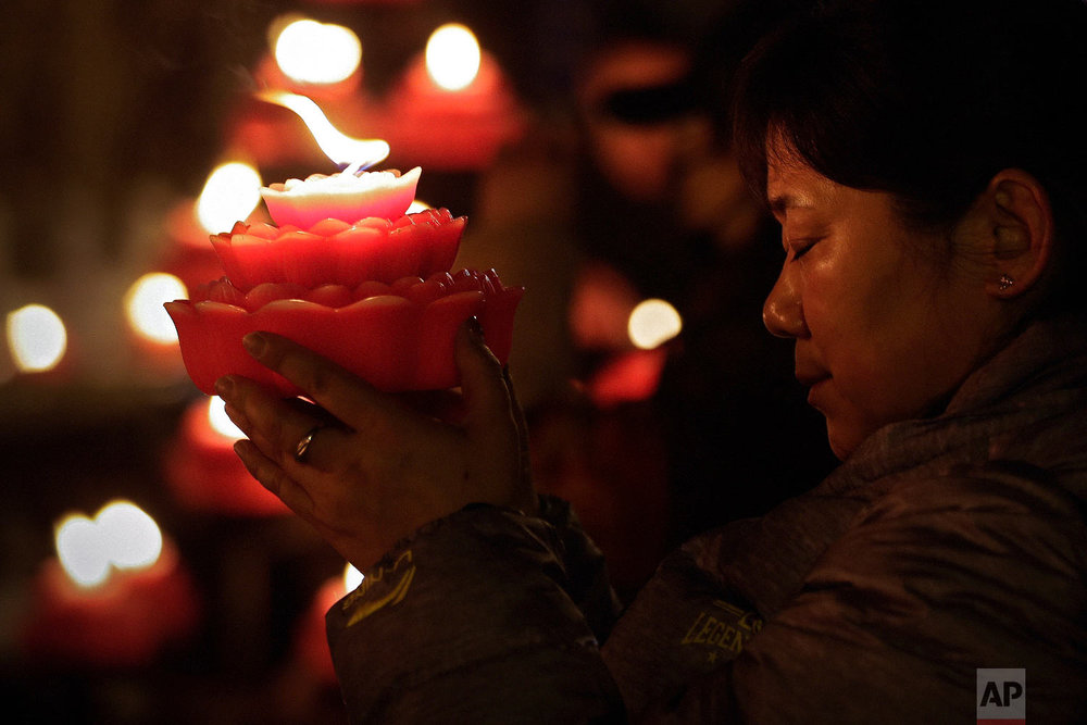 A woman holds a flower-shape candle prays on the first day of the Chinese Lunar New Year at the Tanzhe temple in the Mentougou District of Beijing, Tuesday, Feb. 5, 2019. (AP Photo/Andy Wong)