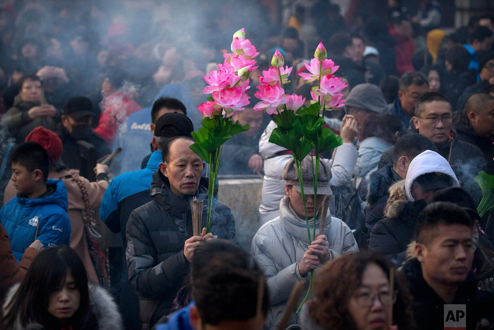 People hold floral bouquets and sticks of incense as they pray at the Lama Temple in Beijing, Tuesday, Feb. 5, 2019. (AP Photo/Mark Schiefelbein)