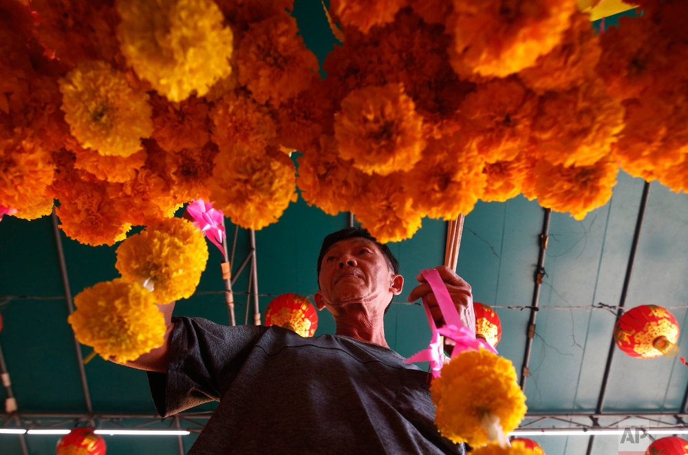 Ethnic Chinese-Thai offers flowers after prayers at the Leng Nuei Yee Chinese temple for the upcoming Lunar New Year in Bangkok, Thailand, Wednesday, Jan. 30, 2019. (AP Photo/Sakchai Lalit)