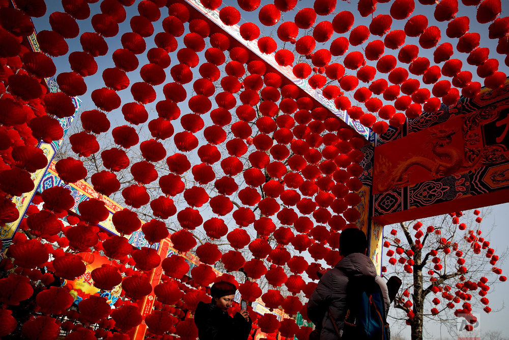A woman takes a souvenir photo of her family posing in front of red lanterns on display at the Longtan Park for a temple fair ahead of Chinese Lunar New Year in Beijing, Sunday, Feb. 3, 2019. (AP Photo/Andy Wong)