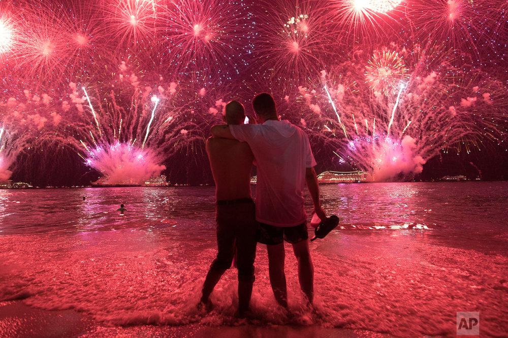Men watch fireworks exploding over Copacabana beach for the New Year's celebrations in Rio de Janeiro, Brazil, Jan. 1, 2019. (AP Photo/Leo Correa)