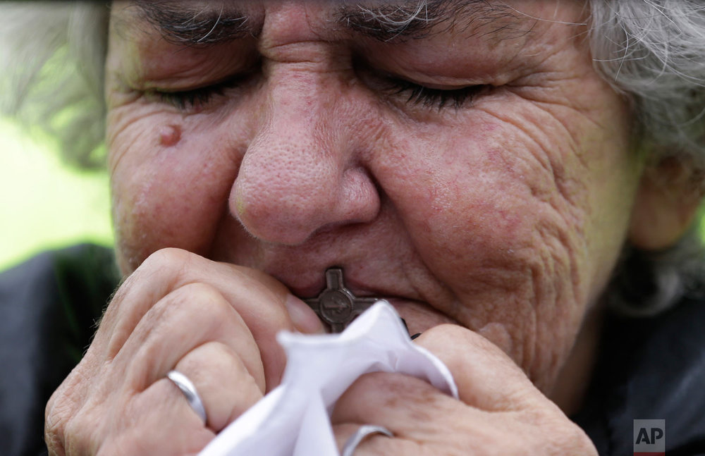 A woman kisses a cross during a rally to protest terrorism in Bogota, Colombia, Jan. 20, 2019. A car bombing at a Bogota police academy that authorities have attributed to rebels of the National Liberation Army killed 21 people and left dozens more wounded on Jan. 17. (AP Photo/Fernando Vergara)