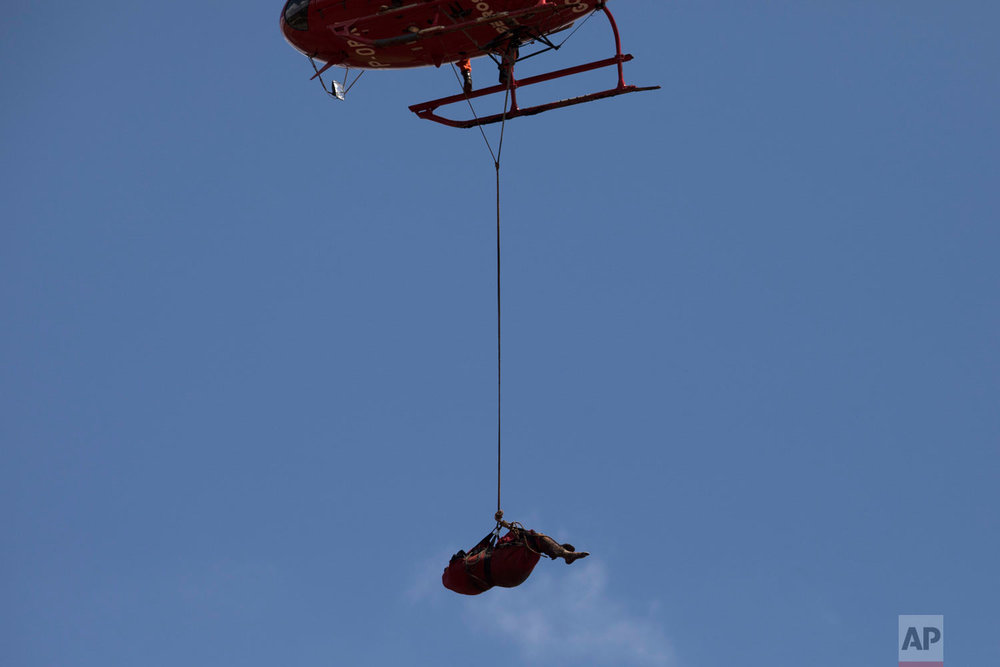 A helicopter lifts a body recovered from the mud days after a Vale mine dam collapsed in Brumadinho, Brazil, Jan. 28, 2019. (AP Photo/Leo Correa, File)