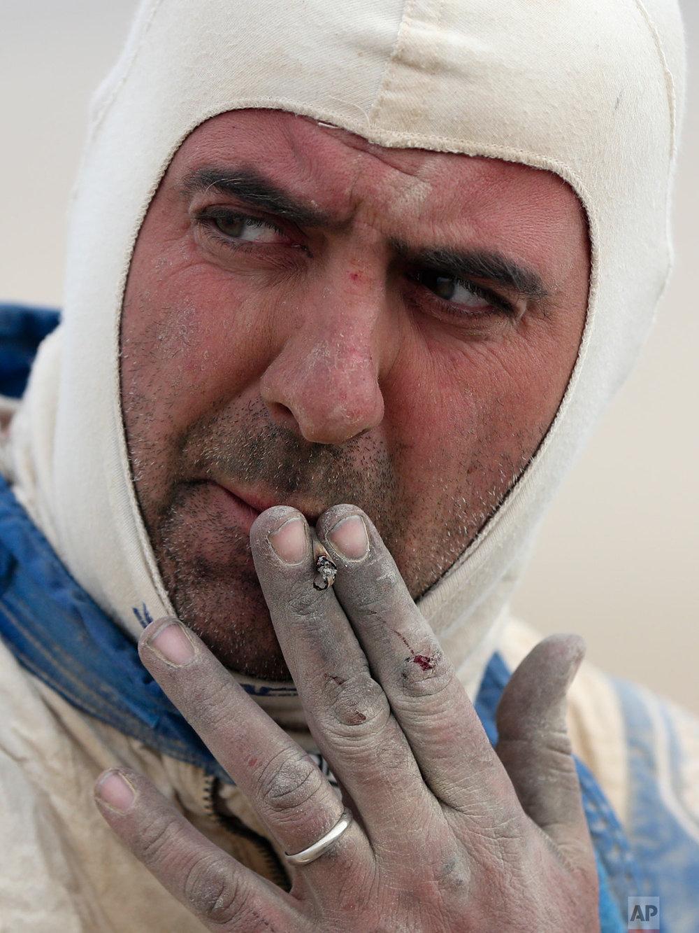 Italian co-driver Angelo Montico smokes as he competes in stage eight of the Dakar Rally, between San Juan de Marcona and Pisco, Peru, Jan. 15, 2019. (AP Photo/Ricardo Mazalan)