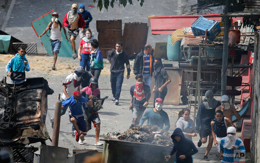 Anti-government protesters run from security forces as they show support for a mutiny by a national guard unit in Caracas, Venezuela, Jan. 21, 2019. Residents set fire to a street barricade of trash and chanted demands that President Nicolas Maduro leave office. (AP Photo/Ariana Cubillos)