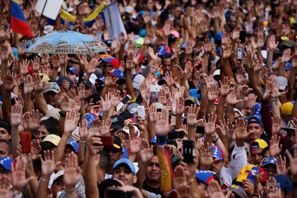 Anti-government protesters hold their hands up during the symbolic swearing-in of Juan Guaido, head of the opposition-run congress, who declared himself interim president of Venezuela, during a rally demanding President Nicolas Maduro's resignation in Caracas, Venezuela, Jan. 23, 2019. (AP Photo/Fernando Llano)