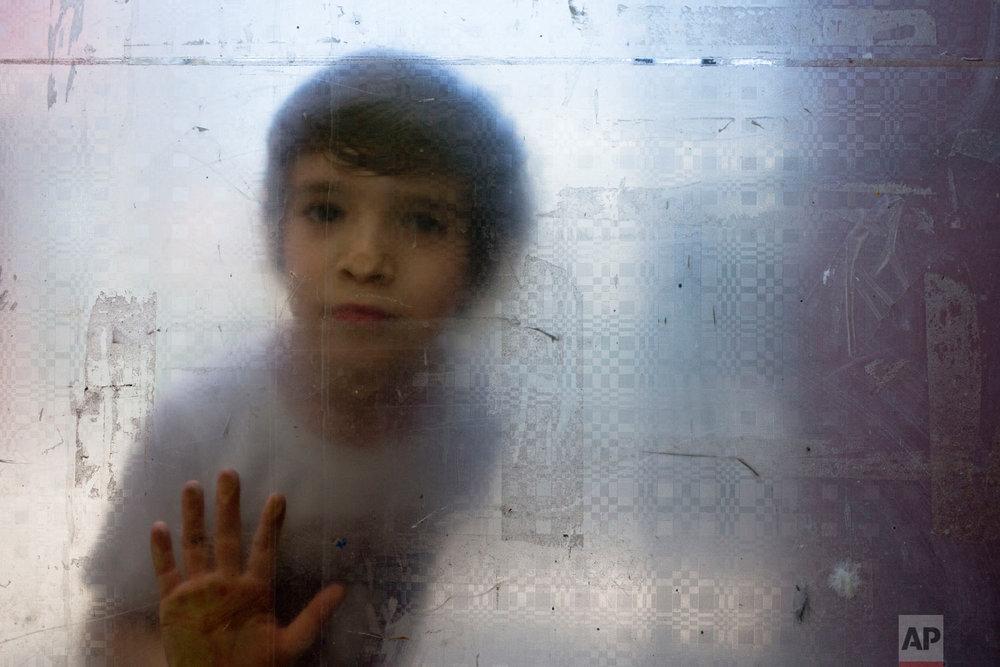 In this Dec.13, 2018 photo published in Jan. 2019, Laura, a transgender girl, looks through a glass door during recess at the Amaranta Gomez school for transgender children in Santiago, Chile. (AP Photo/Esteban Felix)