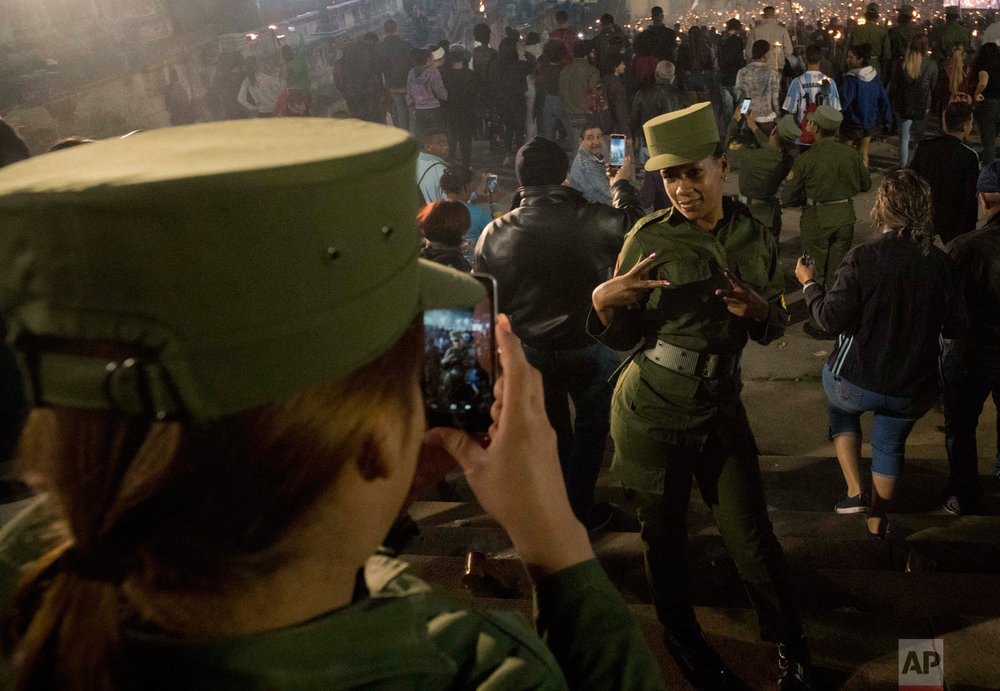 Cuban soldiers take pictures of themselves during the march of torches marking the 166th anniversary of the birth of Cuba's national independence hero Jose Marti and to pay tribute to late revolutionary leader Fidel Castro, in Havana, Cuba, Jan. 28, 2019. (AP Photo/Ramon Espinosa)