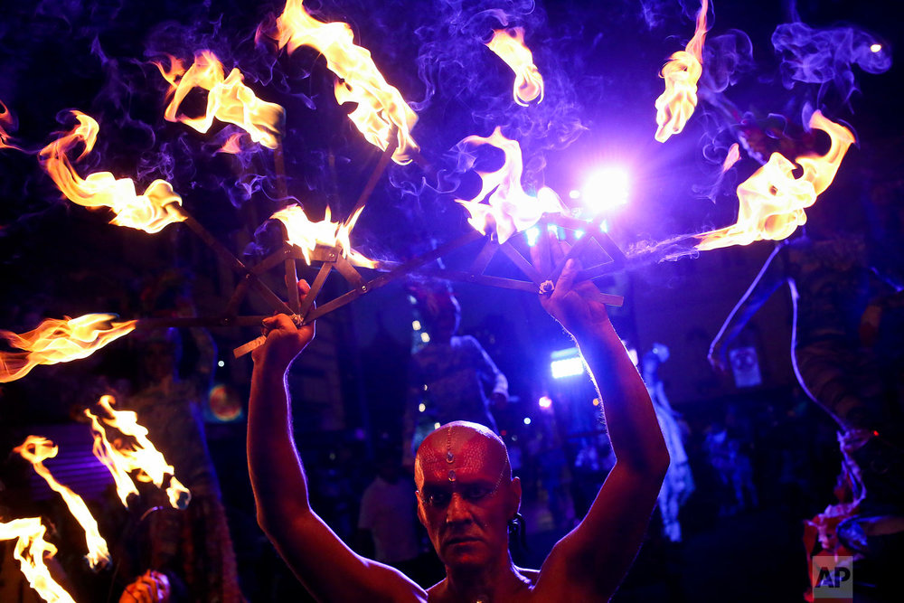 """Dancers perform with fire during the Dance, Theater and Visual Arts International Festival Santiago """"A Mil"""" in Santiago, Chile, Jan. 3, 2019. (AP Photo/Esteban Felix)"""
