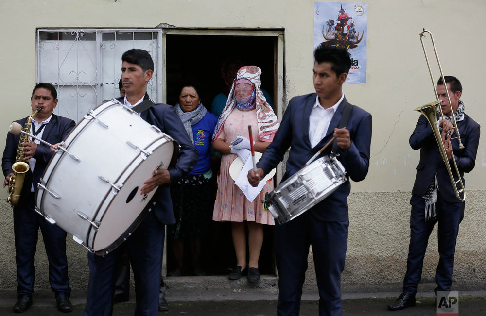 "Musicians and a reveler in costume get ready to participate in the feast of ""La Diablada"" in Pillaro, Ecuador, Jan. 4, 2019. (AP Photo/Dolores Ochoa)"