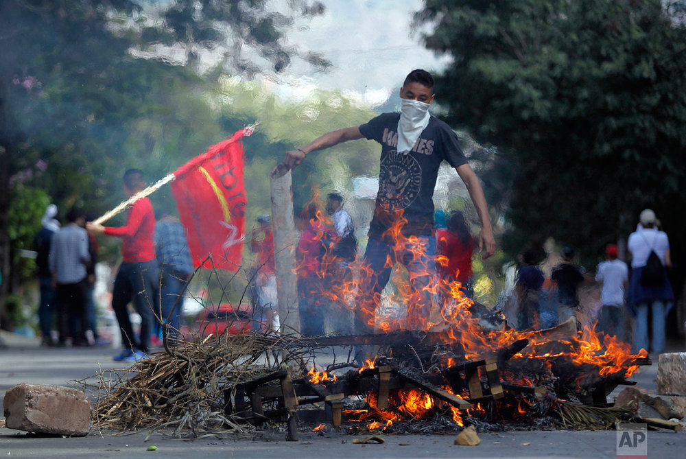 A masked demonstrator adds wood to a burning roadblock during a protest against the government of Honduras' President Juan Orlando Hernandez in Tegucigalpa, Honduras, Jan. 27, 2019, on the anniversary of Hernandez's reelection. (AP Photo/Fernando Antonio)